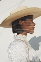 Close up of model wearing straw hat with veil and formal dress