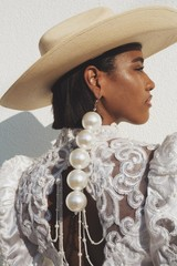 Model in formal dress with oversize pearl earring  and straw hat