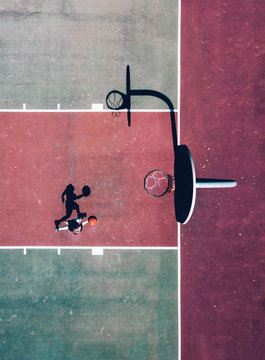 Aerial view of person dribbling basketball towards hoop