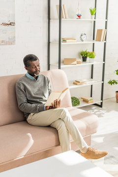 senior african american man sitting on sofa in living room and reading book