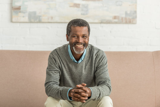 senior african american man sitting on sofa with clenched hands and smiling at camera