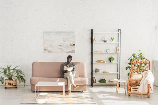 senior african american man reading book while sitting on sofa in living room