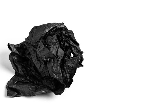Crumpled sheet of black paper on a white background. Copy space.