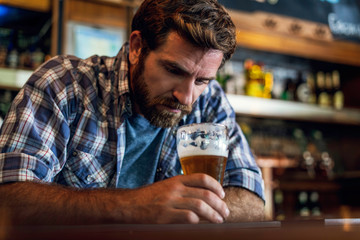 Sad man looking at beer glass while sitting in beer bar