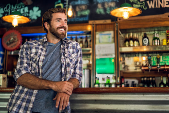 Smiling thoughtful man leaning against bar counter