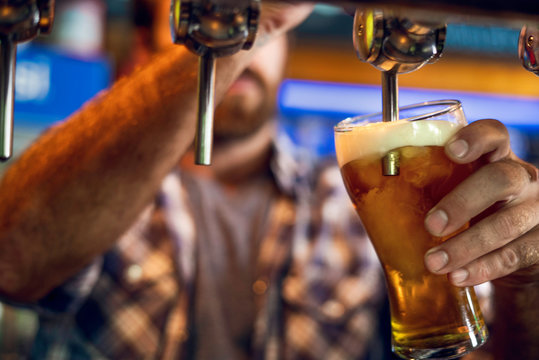 Close-up of man drawing beer from tap into a glass in the bar