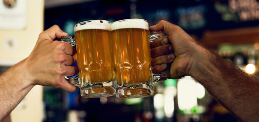 Close-up of hands toasting beer mugs in the bar
