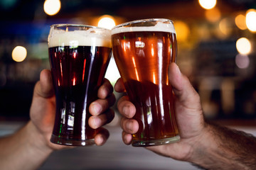 Close-up of hands toasting beer glasses in the bar