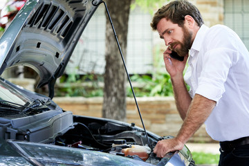 Man talking on mobile phone while standing by broken car