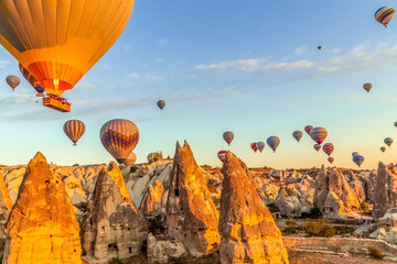 Bright morning as many hot air balloons float in clear skies just above the valleys and homes in Cappadocia