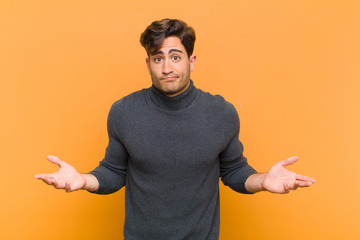 young handsome man feeling clueless and confused, having no idea, absolutely puzzled with a dumb or foolish look against orange background