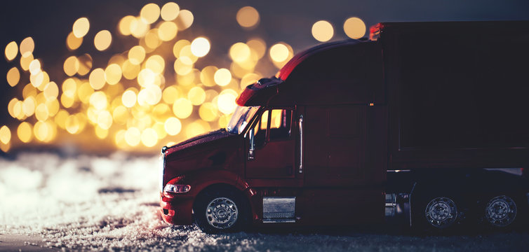 Red toy truck on snow Christmas background.