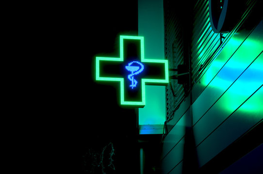 health care medical store cross green sign symbol at front of the shop