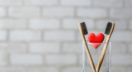 Two toothbrushes in the glass and red heart over brick wall background. Love and Valentines Day concept. Bamboo eco friendly toothbrushes