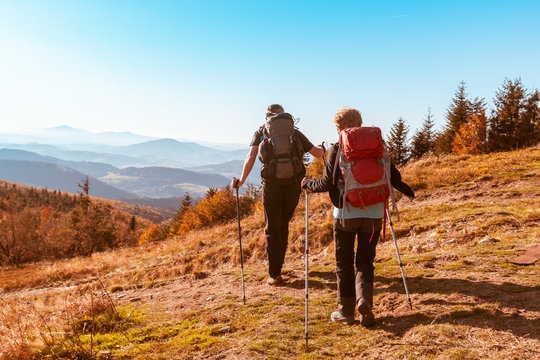 Two old people with large backpacks hike through the autumn mountains, the concept of active recreation in old age