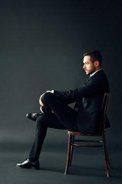 Confident handsome man in black suit sitting on the chair on dark backround