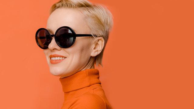Beauty portrait of female model wearing trendy sunglasses over orange background