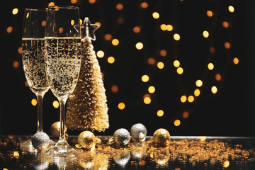 Champagne glasses and baubles against blurred lights background, space for text