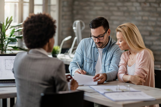 Couple signing a contract on a meeting with real estate agent.