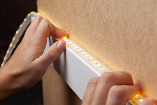 the master glues the LED strip into the niche of the shelf from the cabinet for lighting.installation of diode lighting tape