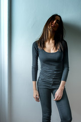 Dark mood portrait of a woman in front of a wall