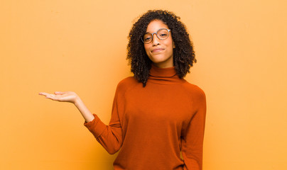 young pretty black woman feeling happy and smiling casually, looking to an object or concept held...
