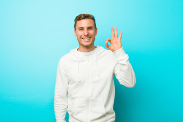 Young caucasian sport man cheerful and confident showing ok gesture.