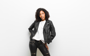young pretty black woman wearing a leather jacket against white wall