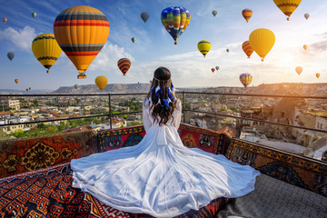 Wall Mural - Beautiful girl sitting on the hotel and looking to hot air balloons in Cappadocia, Turkey.