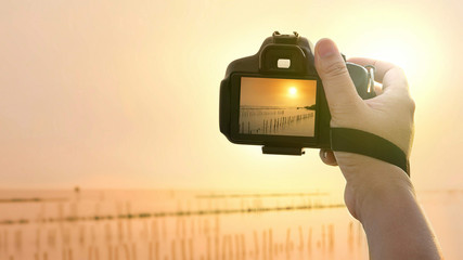Focus on man's hand using camera taking picture of sunset sky at sea viewpoint in morning time