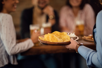 Close-up of waitress serving nacho chips to guests in a pub.