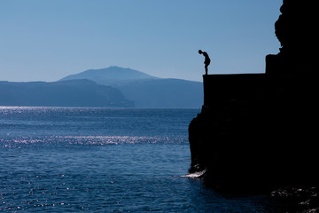 Tourists jumping off a large rock ledge in Amoudi Bay on Santorini Island in Greece.