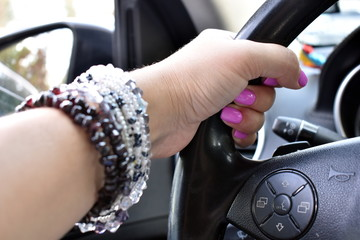 Beautiful female hand holds the steering wheel. Stylish natural bracelets on a female hand.