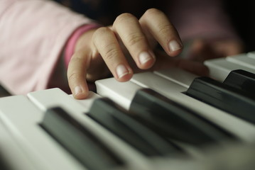 children's hand are playing the piano