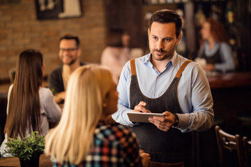 Waiter taking an order on touchpad while serving a guest in a bar.