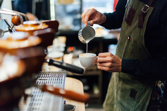 Barista making coffee in coffee shop, hands holding cup of coffee.