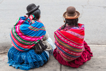 Two women with braids wearing traditional clothes sit on the streets of Puno city in Peru