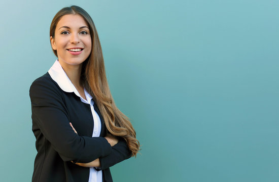 Smiling business woman with suit standing against blue background with crossed arms outdoor. Copy space.