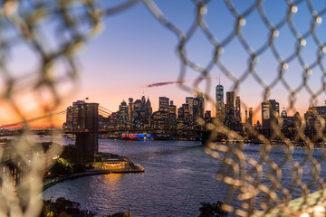 View of Manhattan and the Brooklyn Bridge through a Manhattan Bridge fence opening in the sunset
