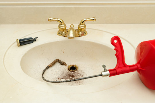 Plumbing snake with hair clog in a bathroom sink with a shallow depth of field