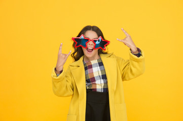 She goes crazy. Crazy child show horns sign hand gesture. Happy girl with crazy look yellow background. Fashion kid wear star shaped glasses. Crazy holiday mood. School holidays