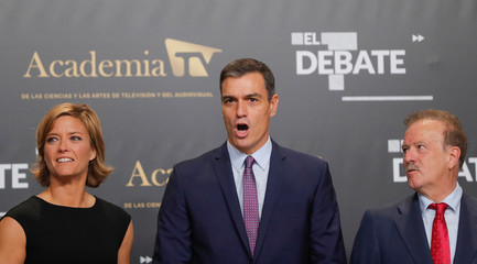 Spanish acting Prime Minister and Leader of Socialist Workers' Party (PSOE) Pedro Sanchez reacts as he poses for a picture with debate moderators Manuel Campo Vidal and Maria Casado before a televised debate ahead of general elections in Madrid