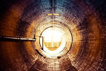 Staring down an old tunnel with a light at the end of the tunnel.  This is a ventilation tunnel inside the Hoover Dam.