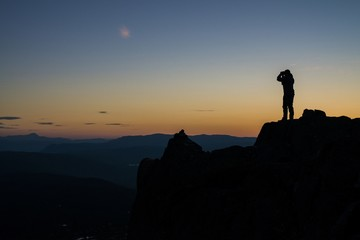 Silhouette of a person standing on a cliff and taking a picture of the beautiful sunset