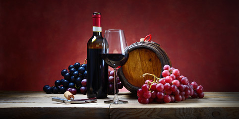 Red wine glass with bunches of grapes, bottle and small barrel. Space for text.