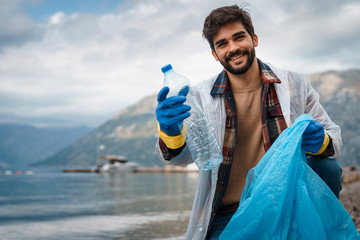 Young man holding plastic bottle while looking at camera at beach - Stock Photo