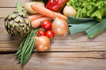 Fresh vegetables on wooden background, top view.