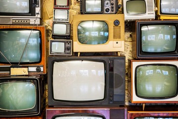 Many old televisions bundled together. A wall of old vintage tube televisions