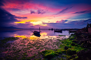 Colorful sunset on the lagoon with, fishermen's boat moored. Idyllic scene with specular reflection on the sea.