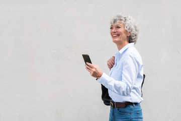 happy older woman walking with handbag and cellphone by white background